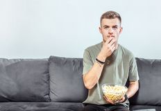 Intensed Boy Watches Stressful Film. Intensed fair hair boy watches a horror film, eating popcorn on the comfortable grey sofa, stressful emotion Stock Photos