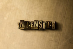 INTENSITÀ - primo piano della parola composta annata grungy sul contesto del metallo fotografie stock