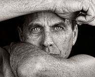 Intensity. Distressed man framing his face with his arms Royalty Free Stock Photo