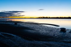Intensity of Tauranga sunrise across harbor as light of sky and. Dark of foreground beach contrast Royalty Free Stock Photo