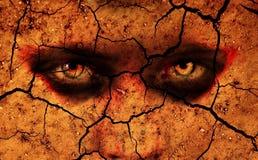 Intensiva ögon som ut ser från sprucken jordning Royaltyfri Bild