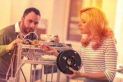 Intensiva kontorsarbetare som försöker att sätta tillsammans delarna för en skrivare 3D arkivfoton