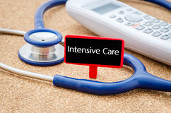 Intensive care words. Phone and stethoscope on the table with Intensive care words on the board. Medical concept royalty free stock photos