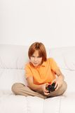 Intensive video game. Little boy with tense expression holding game controller of videogame sitting on the coach Stock Image