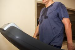 Intensive workout on treadmill, cardio training. Sweaty man having intensive training on treadmill in the gym. Cardio exercising and weight loss Royalty Free Stock Image