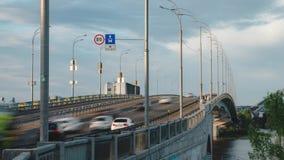 Intensivt trafikflöde till och med bron och ett bilanseende på trottoarkanten med larm vände på lager videofilmer
