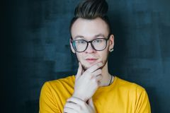 Intent curious emotional hipster guy portrait. Portrait of curious hipster guy with comb over haircut. Young emotional man in glasses ing chin. Intent facial royalty free stock images