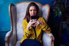 Intent girl looking attentively at the screen of a smartphone Royalty Free Stock Photos