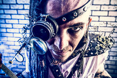 Intent look. Portrait of a steampunk man with a mechanical devices over brick wall stock photography