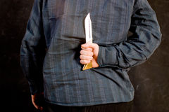 Intent to kill. Man with a knife behind his back stock photography