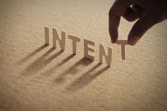 INTENT wood word on compressed board. With human& x27;s finger at T letter royalty free stock image