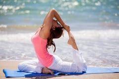 Intentar algunas actitudes de la yoga en la playa Fotos de archivo