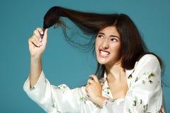 Intento adolescente divertido de la muchacha para bombardear su pelo por la mañana Fotografía de archivo