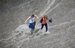 Intento de la gente para cruzar un camino inundado   Foto de archivo