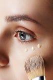 Intento de la muchacha de la belleza a diversos tonos del lápiz corrector de la fundación Maquillaje natural para la mujer morena imagen de archivo