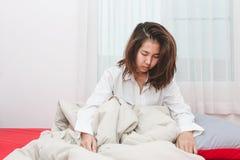 Intento de la mujer de Asia a despertar en la mañana en su sitio de la cama Imagenes de archivo