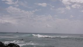 Intento de las personas que practica surf para coger una ola oceánica grande almacen de metraje de vídeo