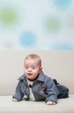 Intento del bebé a arrastrarse en el sofá Foto de archivo