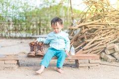 Intento tailandés del bebé al father& que lleva x27; botas de s Fotografía de archivo