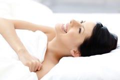 Intentos atractivos de risa de la muchacha a bajar dormido Fotografía de archivo libre de regalías