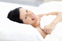 Intentos de risa de la mujer a bajar dormido Imagenes de archivo