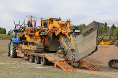 Inter-Drain Trencher Transport on Work Site. SALO, FINLAND - MAY 25, 2017: Inter-Drain 2028T trencher transported on a tractor trailer and other heavy equipment stock images