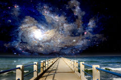 Inter-Galactic Space Beach. Abandoned jetty against a backdrop of a beautiful sea and galaxies at Terengganu, Malaysia Royalty Free Stock Images