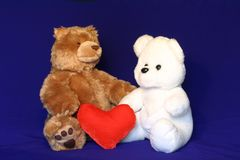 Inter racial couple 1. A brown and a white teddy bears holding a love symbol. could be used for inter racial love/marriage related material Royalty Free Stock Photography