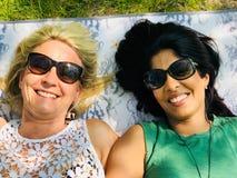 Inter-ras- glade par som tycker om en utomhus- picknick Arkivfoton