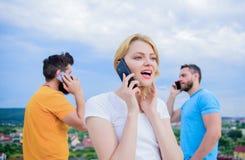 Interação um com o outro com a tecnologia Grupo de amigos que falam em telefones celulares Povos que usam o móbil fotografia de stock