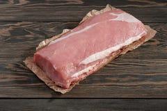 Intera lonza di maiale senz'ossa senza grasso Filetto di carne di maiale su carta su un fondo scuro fotografie stock
