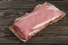 Intera lonza di maiale senz'ossa senza grasso Filetto di carne di maiale su carta su un fondo scuro fotografia stock libera da diritti