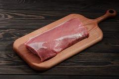 Intera lonza di maiale senz'ossa senza grasso Filetto di carne di maiale su un tagliere su un fondo scuro immagini stock libere da diritti