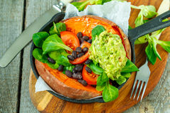 Intera patata dolce al forno con guacamole ed i fagioli neri in una padella della ghisa Fotografia Stock Libera da Diritti