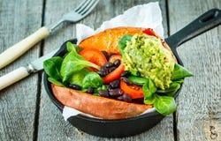 Intera patata dolce al forno con guacamole ed i fagioli neri in una padella della ghisa Fotografia Stock