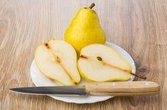 Intera pera gialla, metà della pera e coltello in piatto Immagine Stock Libera da Diritti