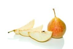 Intera pera giallo-rossa e poche fette Fotografie Stock