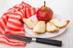 Intera pera, pezzi di pera in piatto, tovagliolo rosso, coltello Fotografia Stock