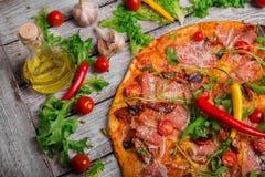 Intera pizza italiana con i peperoncini e le merguez luminosi Una vista superiore della pizza calda della carne su un fondo rusti immagine stock