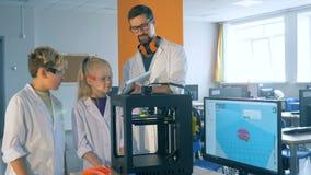 Interacción entre un técnico de laboratorio y dos niños mientras que maneja la impresión 3D almacen de metraje de vídeo