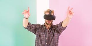 Interactie in virtuele werkelijkheid met digitale oppervlakte Mensen ongeschoren kerel met VR-glazen, roze achtergrond Hipstergeb stock foto
