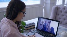 Interactieve opleiding, vrouwelijke student in oogglazen met pen die in blocnote tijdens het letten op video op een notitieboekje stock videobeelden