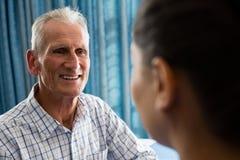 interactin d'homme supérieur avec le docteur féminin dans la maison de retraite Image libre de droits