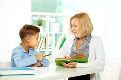 Interacting at lesson. Portrait of diligent boy and his tutor interacting with each other Royalty Free Stock Photos