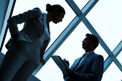 Interacting partners. Two silhouettes of businesspeople interacting with each other in the office Stock Photos