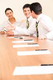 Interaction. Vertical photo of businessmen discussing new strategy on the background of smiling woman looking at them Royalty Free Stock Photography