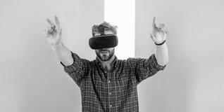 Interaction dans la réalité virtuelle avec la surface numérique Équipez le type non rasé avec des verres de VR, fond rose Utilisa photo stock