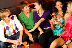 Interaction at a party. Portrait of five happy people sitting on the sofa and interacting at evening-party stock photography