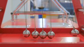 Newton`s cradle work. Interactive exposition in science museum. Demonstration of Newton`s cradle work at technology museum. Science and physics concept stock footage