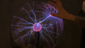 Woman touching plasma ball